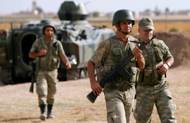 Turkish soldiers walk as they stand guard on the Turkish-Syrian border near the Akcakale border crossing